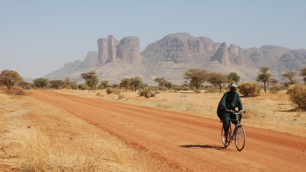 Malian man on bicycle in Sahara desert, Mali, October 2005