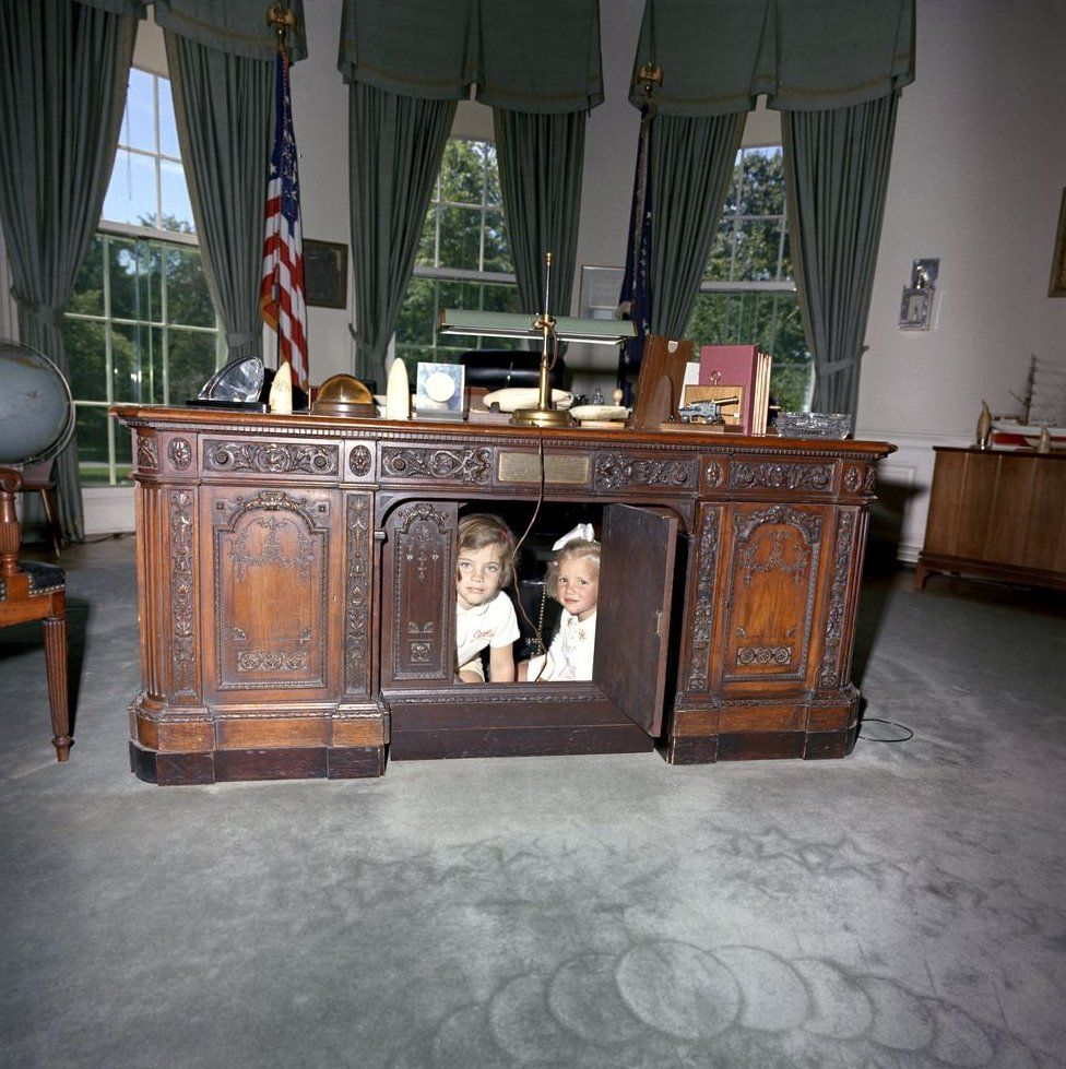 Caroline Kennedy and Kerry Kennedy, daughter of Attorney General Robert F. Kennedy, look through hinged panel of President John F. Kennedy's desk (HMS Resolute Desk) in the Oval Office, White House, Washington, D.C.