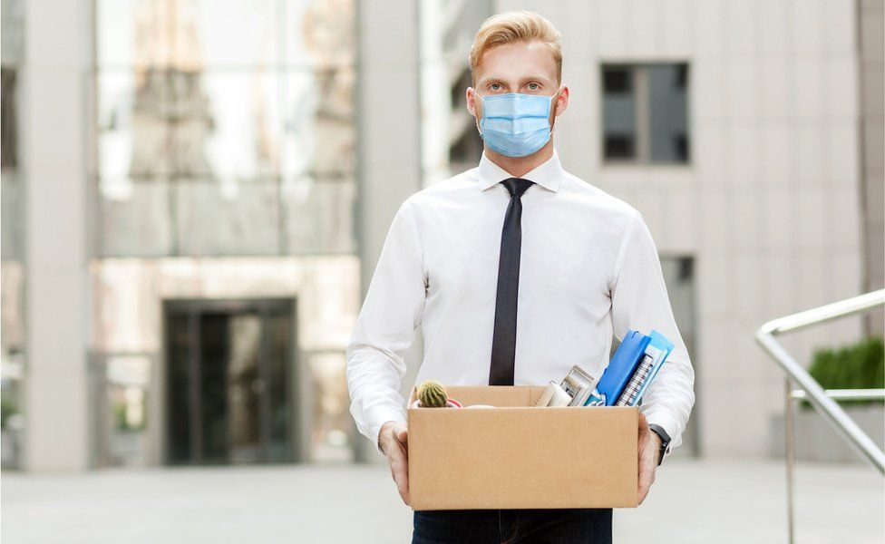 Stock image of a man in facemask carrying a box of his belongings from the office