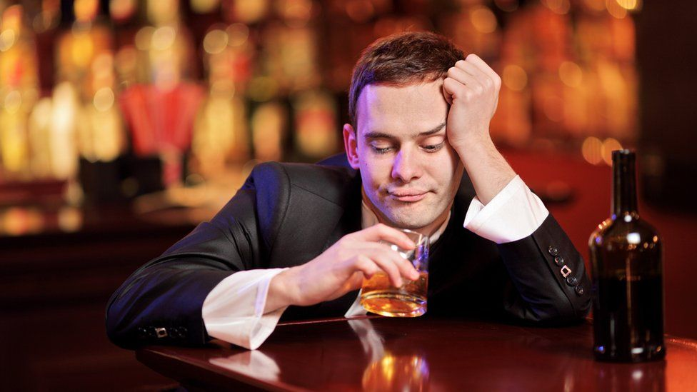A drunk young man drinking and slouching on the bar