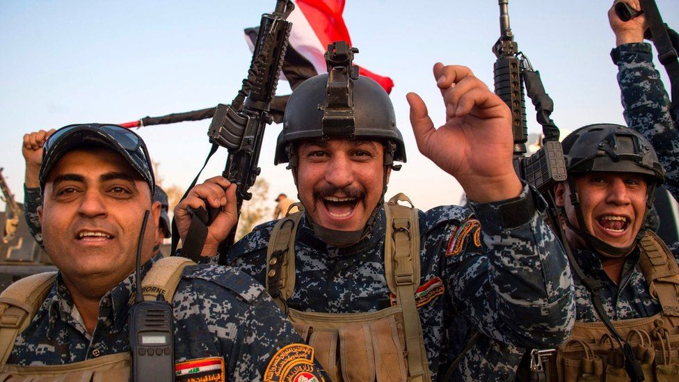 Members of the Iraqi federal police celebrate in the Old City of Mosul on 10 July 2017
