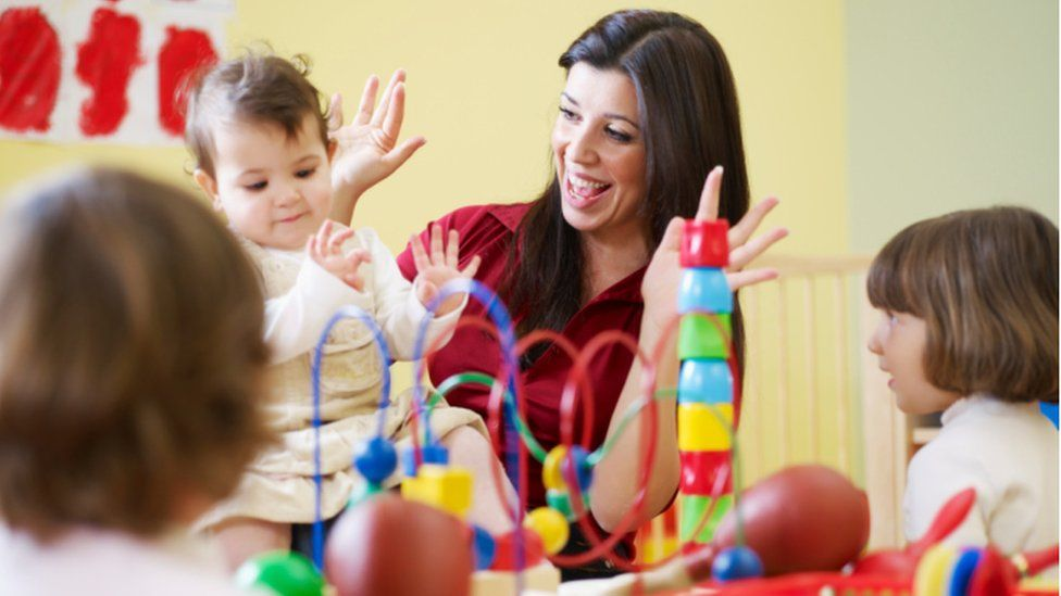 Nursery worker with baby