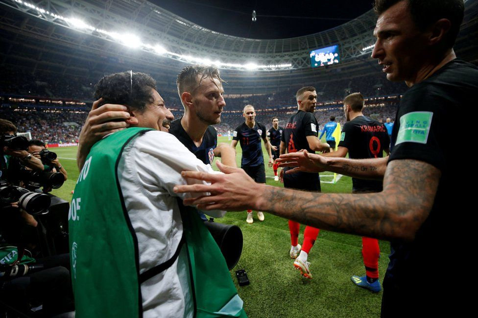 Croatia's Ivan Rakitic and Mario Mandzukic celebrate with an AFP photographer Yuri Cortez after their second goal