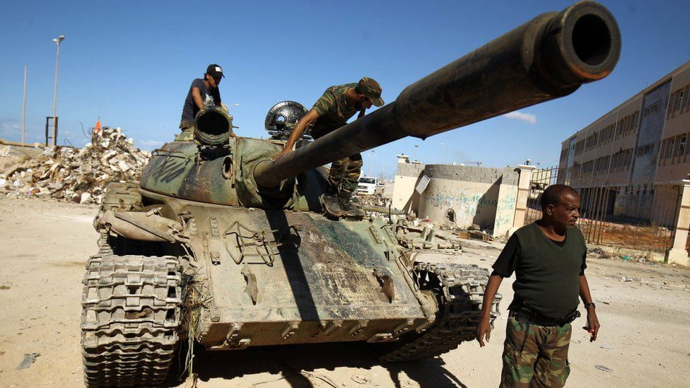 A picture taken on November 9, 2017 shows members of the self-styled Libyan National Army, loyal to the country's east strongman Khalifa Haftar, riding on a tank as it drives down a street through the rubble in Benghazi's central Akhribish district following clashes with militants
