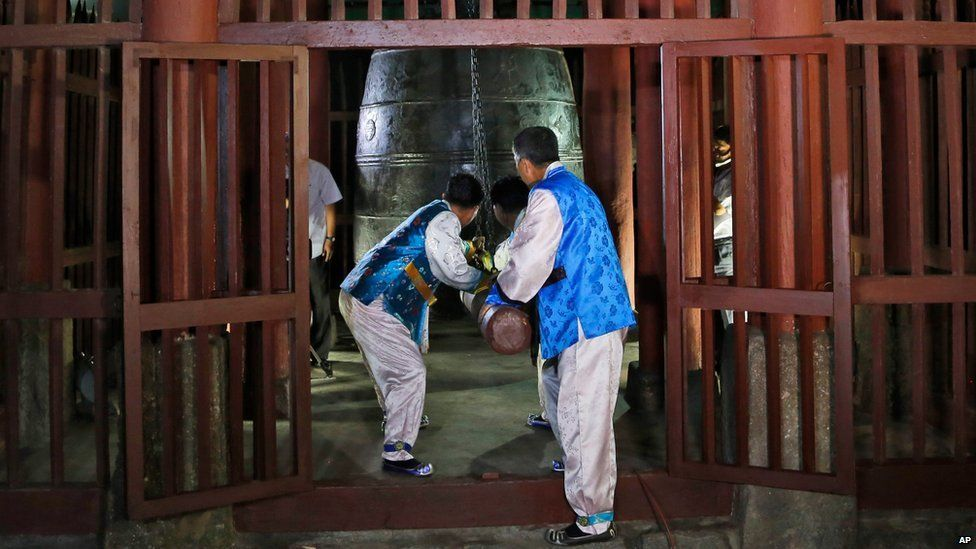 Men in traditional outfits ring a bell to mark the new time zone in a ceremony in Pyongyang on 15 August 2015