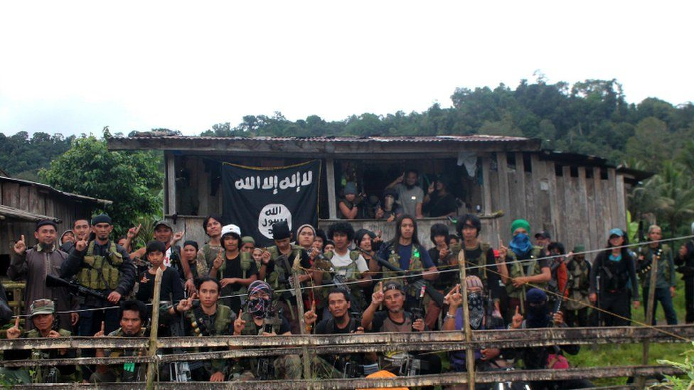Group of Abu Sayyaf fighters with an Islamic State flag