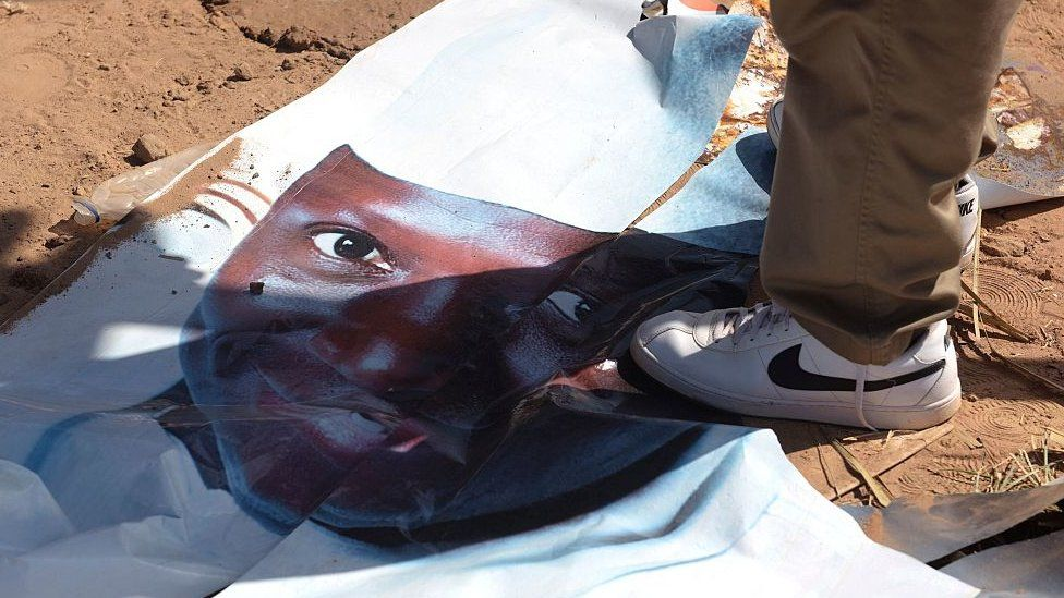 Someone standing on a torn poster of Yahya Jammeh after he lost elections in December 2016