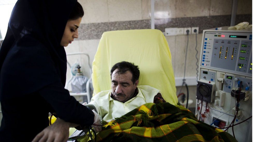 An Iranian nurse measures the blood pressure of a patient at the dialysis ward at the Helal Iran Clinic - file picture