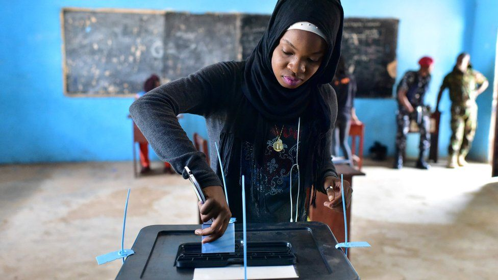A woman casts her vote in a ballot box at the polling station in Freetown on March 31, 2018 during the second round of Sierra Leone's presidential election