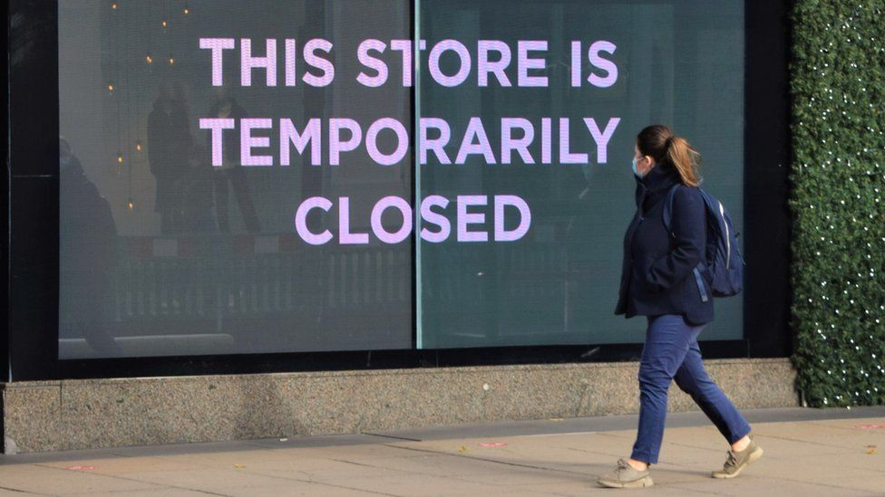 Woman in mask walks past shop sign saying 'This store is closed'