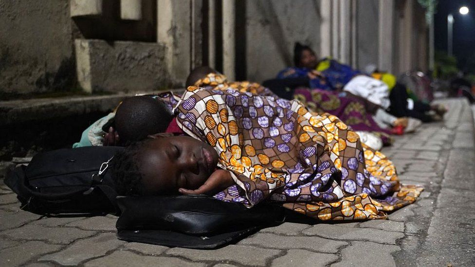 Congolese fleeing from Goma, Democratic Republic of Congo (DRC), sleep with their belongings on a street after the Nyiragongo volcano erupted near the border in Gisenyi, Rwanda, on 23 May 2021