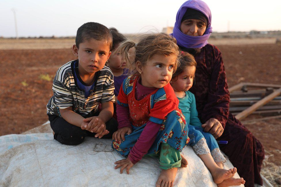 Syrian children and a woman sit near a camp for displaced civilians in Idlib province, Syria (1 September 2018)