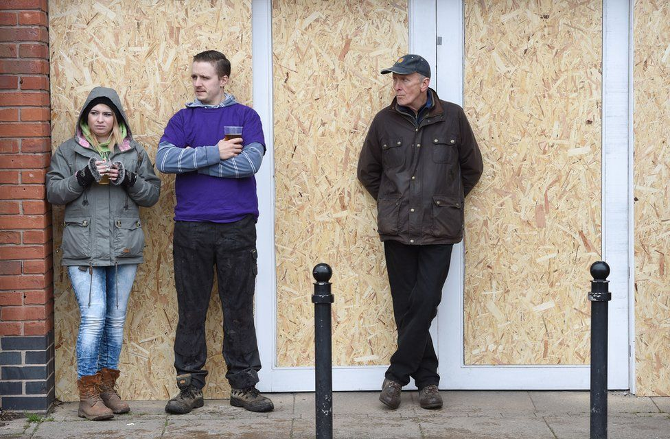 People stand in front of a boarded up shop in Ashbourne, Derbyshire, ahead of the Royal Shrovetide Football match