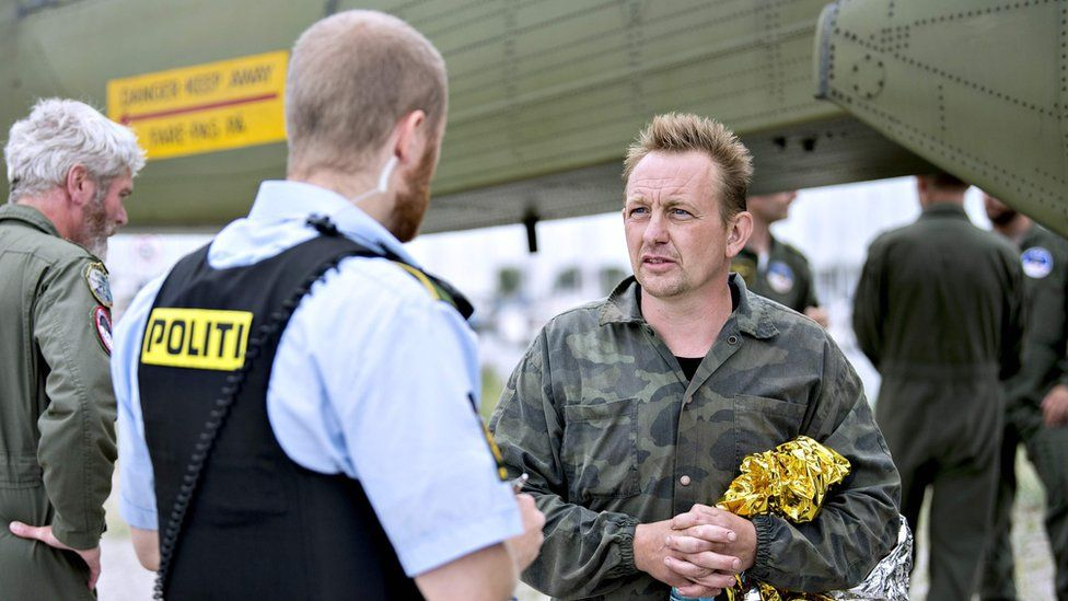 Peter Madsen talks to a police officer in Dragoer Harbor south of Copenhagen on August 11, 2017