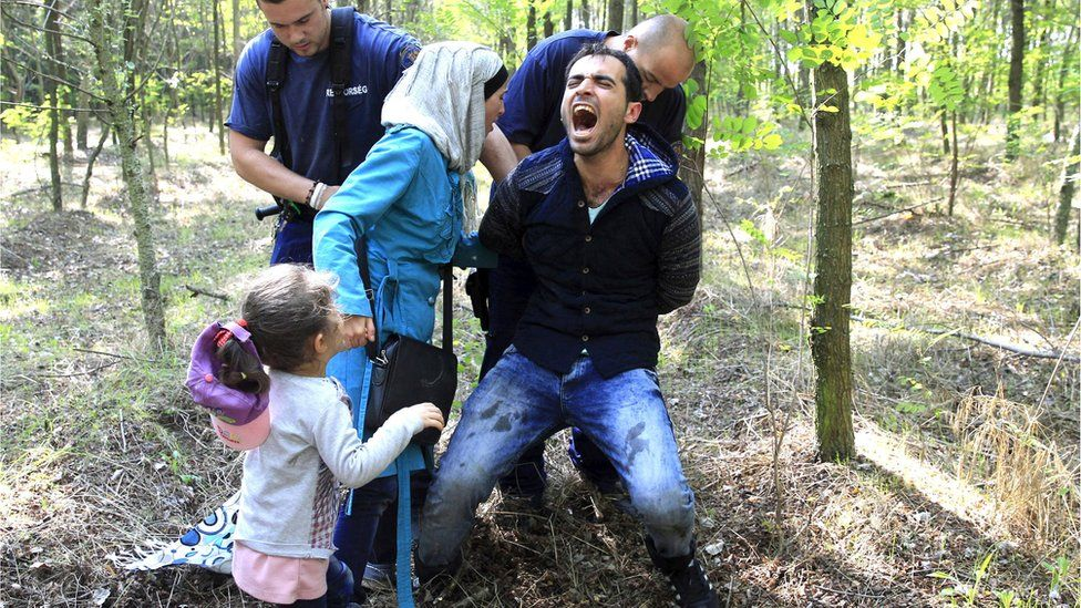 Hungarian policemen detain a Syrian migrant family after they entered Hungary at the border with Serbia, near Roszke, on 28 August, 2015