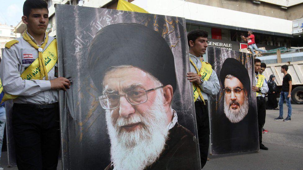 Os partidários do Hezbollah carregam cartazes do líder do Hezbollah Hasan Nasrallah (R) e o líder supremo do Irã, Ayatollah Ali Khamenei, na cidade do sul do Líbano, Nabatieh, em 8 de novembro de 2017