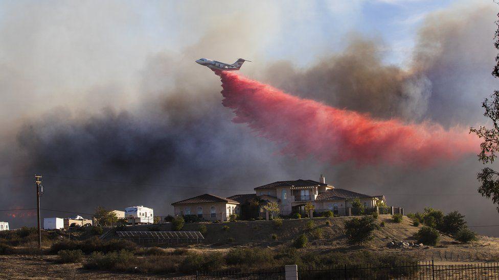 Un avión lanza un retardador de fuego cerca de una casa en Murrieta, California el 7 de diciembre de 2017