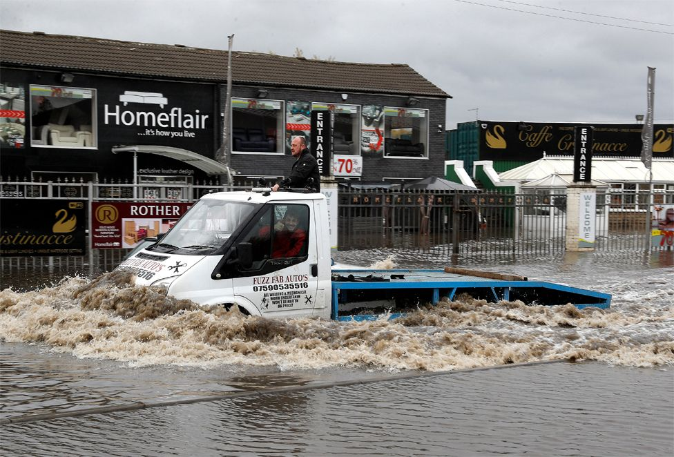 A man drives a truck through flood waters
