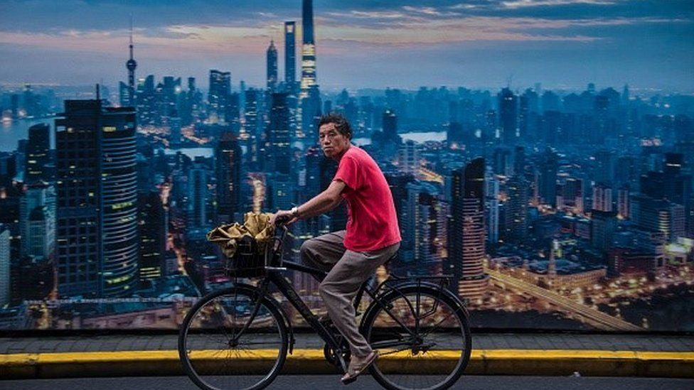 This picture taken on July 11, 2016 shows a man cycling past a billboard showing an aerial view of Shanghai