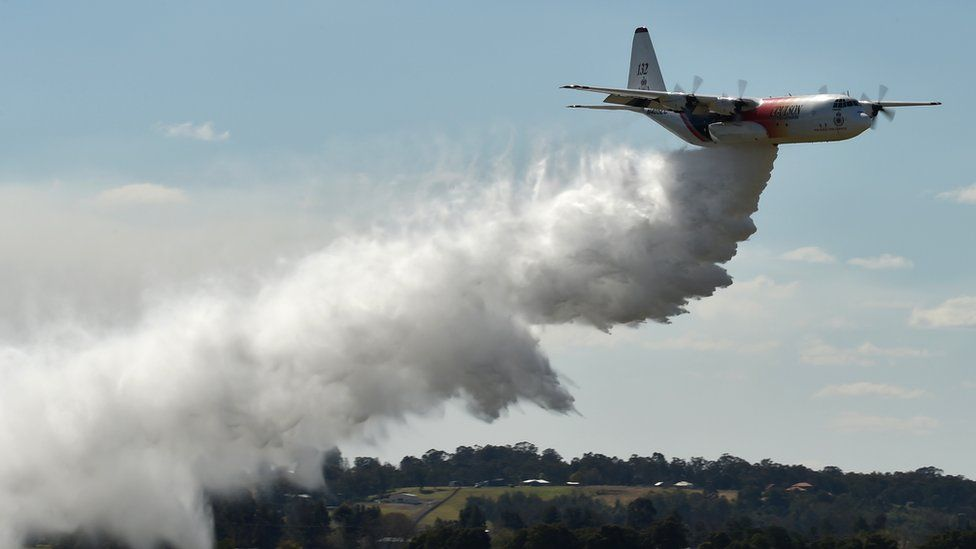 A NSW Rural Fire Services Hercules C-130 large air tanker drops water in an exercise over western Sydney in 2017