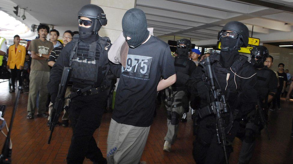 Indonesian anti-terror police from Densus 88 escort four Turks arrested on arrival at Jakarta airport on September 14, 2014