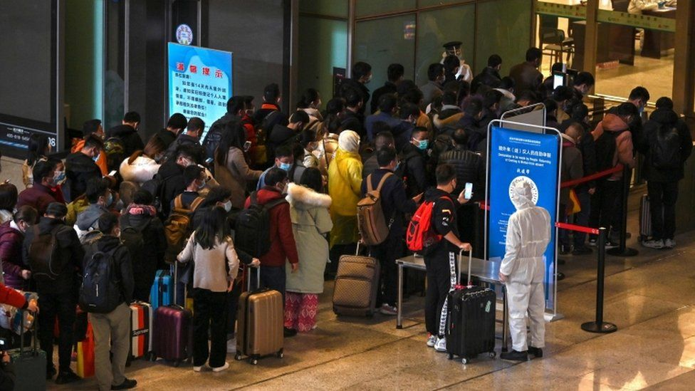 Mask-clad passengers wait in a line after arriving at the railway station in Wuhan, China's central Hubei province on 28 March 2020