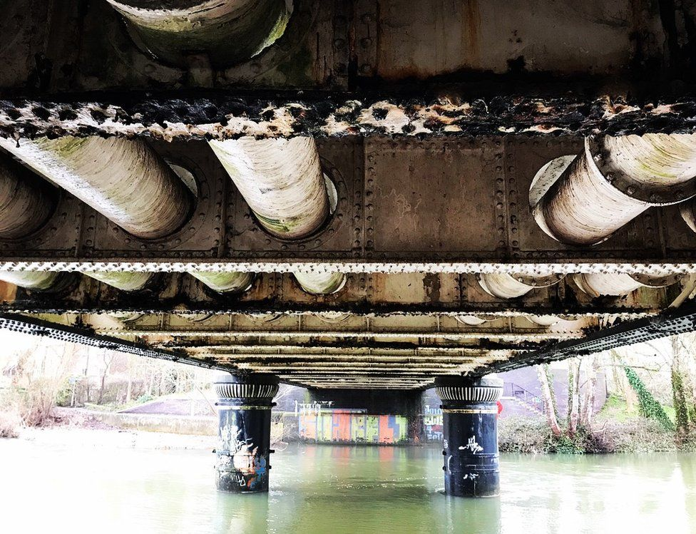 Underneath of a bridge reflected in water