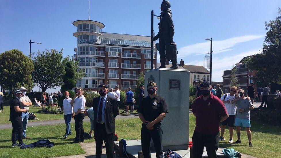 Veterans surround a war memorial