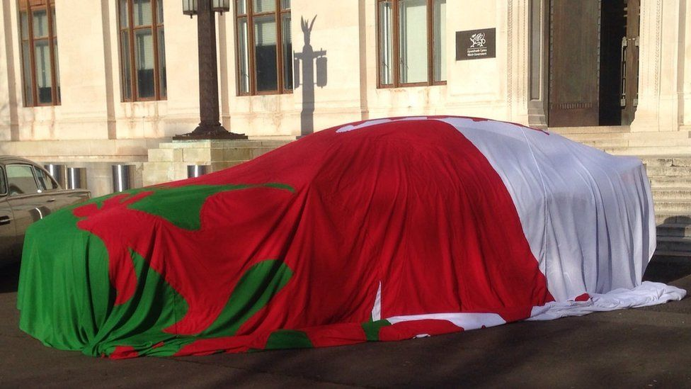2016: The new Aston Martin draped in a Welsh flag outside the Welsh government offices in Cardiff