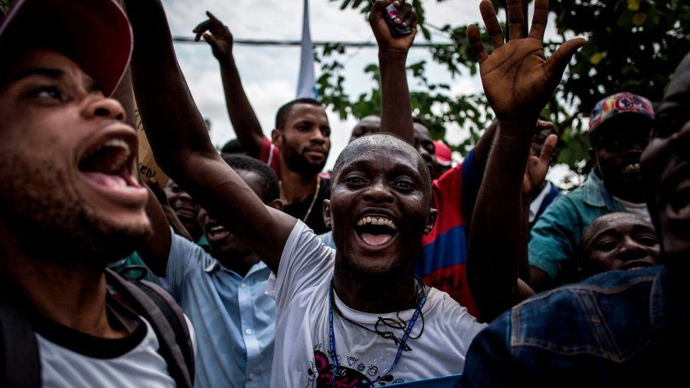 Supporters of Democratic Republic of Congo joint opposition presidential candidate Martin Fayulu sing and dance ahead of his arrival in Kinshasa to launch his campaign on November