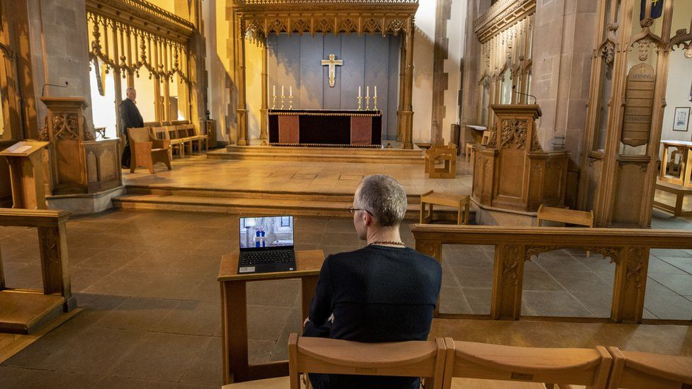 A church parishioner watches a laptop inside Liverpool Parish Church (Our Lady and St Nicholas) in Liverpool