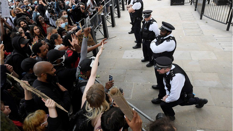 A white police office kneels outside Downing Street