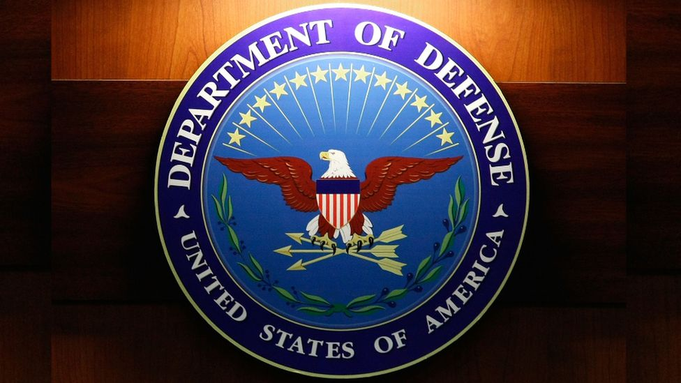 A light shines on the seal of the Department of Defense