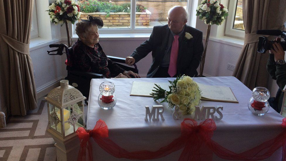 """The newlyweds at a table with a sign saying """"Mr & Mrs"""""""