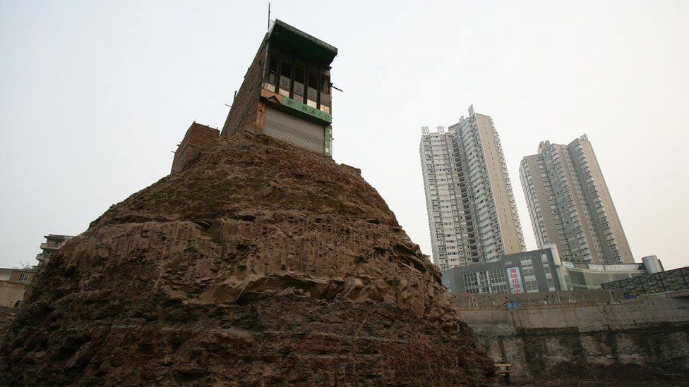 Chongquing, China, 21 March 2007. A house, whose owner refused to accept a compensation deal by a property developer, is surrounded by excavated land at a construction site.