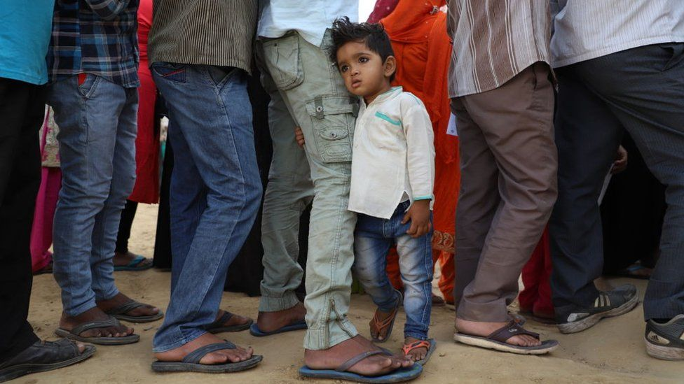 A little boy clutches his father outside a polling booth in Ghaziabad in Uttar Pradesh state