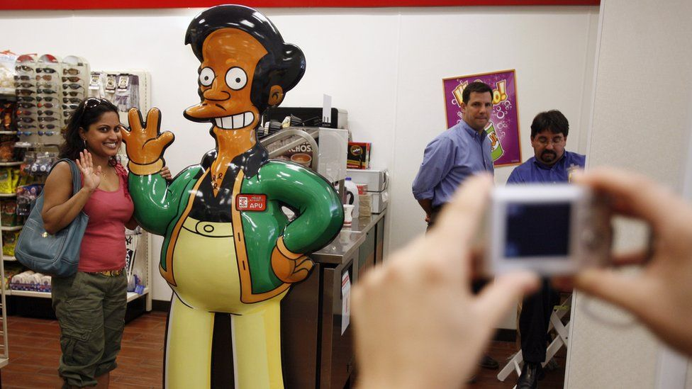 A woman poses for a photograph alongside cartoon statue of character of Apu