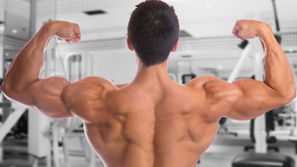 A shirtless man flexing his biceps