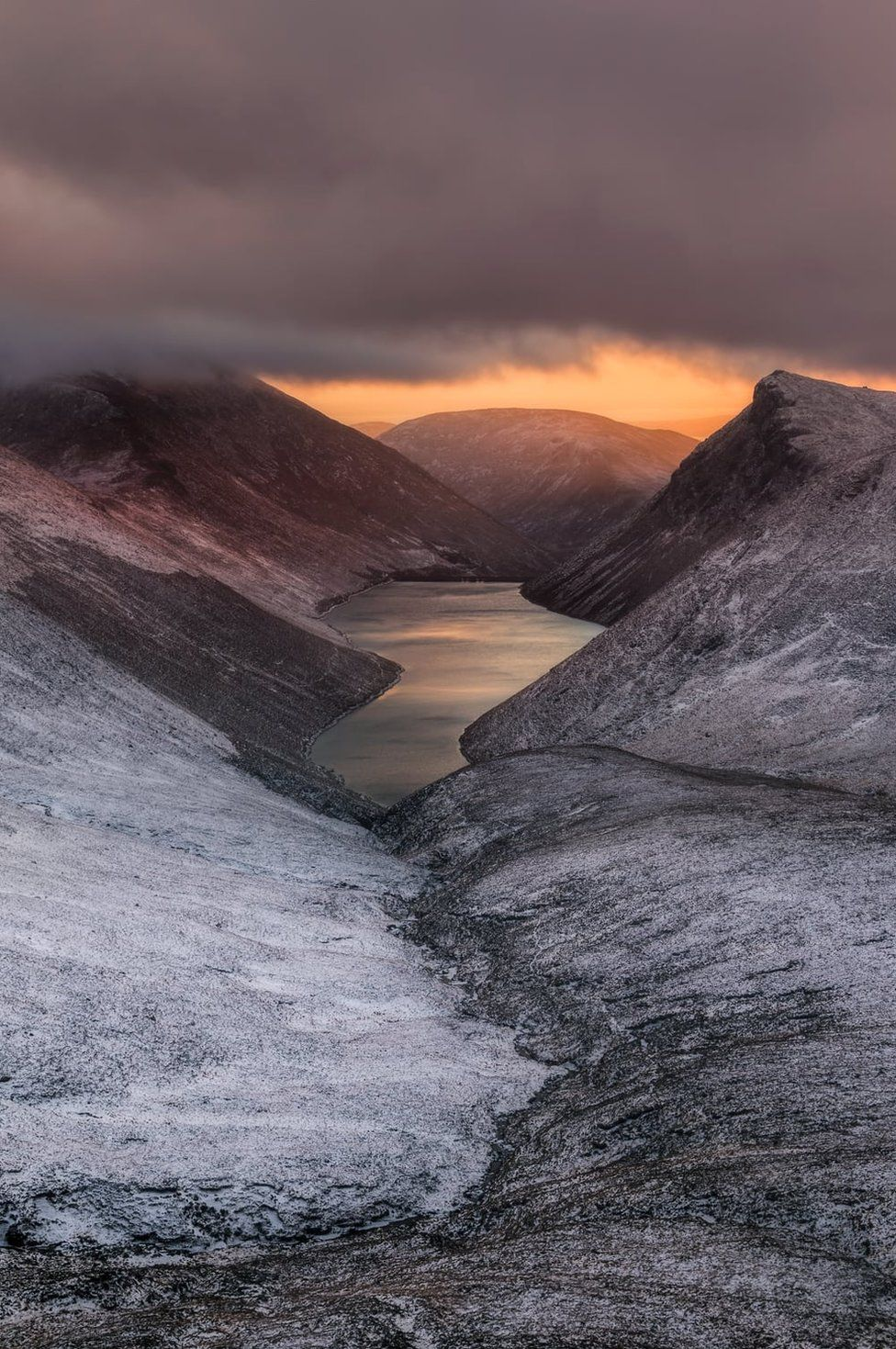 Sunset over Ben Crom reservoir with snow dusting the neighbouring land as seen from Slieve Corragh in the Mourne mountains in County Down