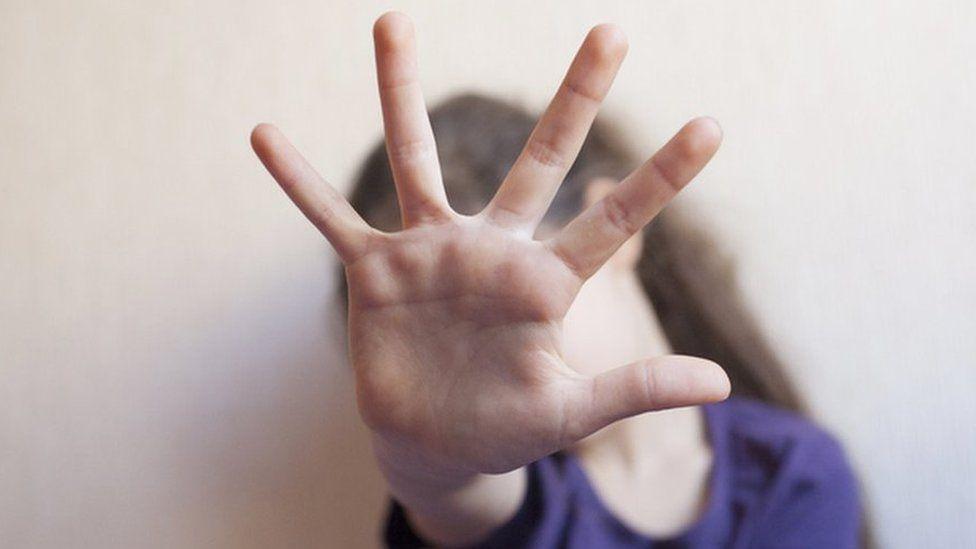 Criança com mão na frente do rosto