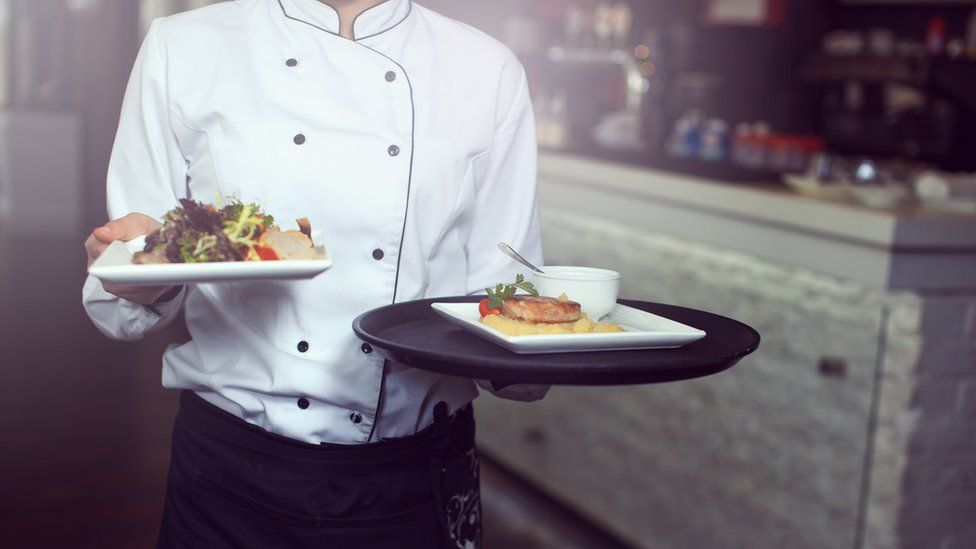 A waiter serving food