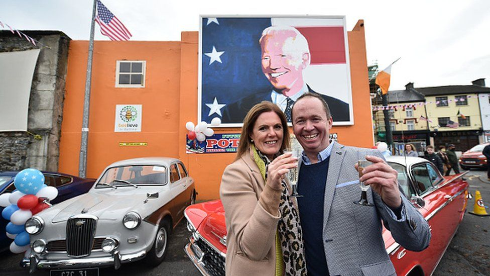 Joe Blewitt and his wife Deirdre drink champagne underneath a mural of their third cousin Joe Biden