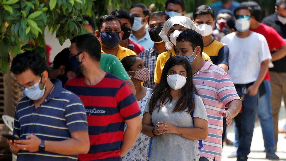 People wearing protective face masks wait to receive a dose of COVISHIELD, a coronavirus disease (COVID-19) vaccine manufactured by Serum Institute of India, outside a vaccination centre in Ahmedabad, India, May 1, 2021
