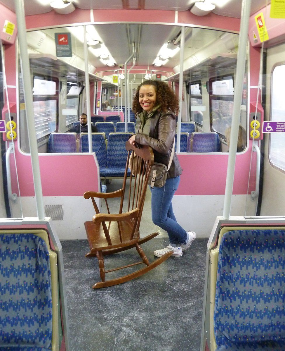 A woman stands on a train carriage with a rocking chair