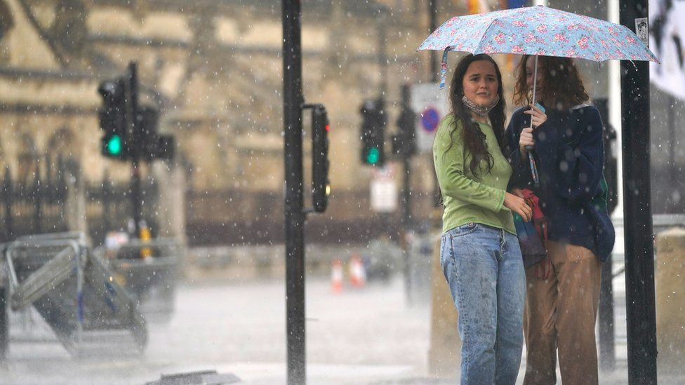 Two young women shelter under an umbrella in Parliament Square in central London amid heavy rain