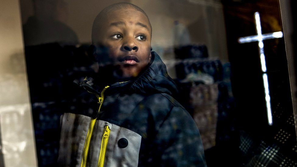Boy looks at stacks of water in Flint