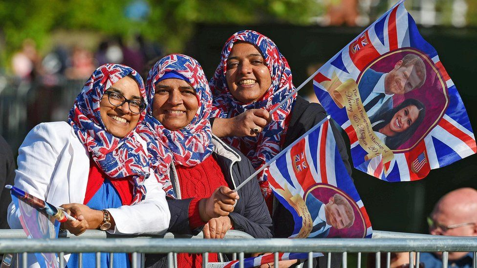 Three girls wearing Union Jack headscarves and waiving flags
