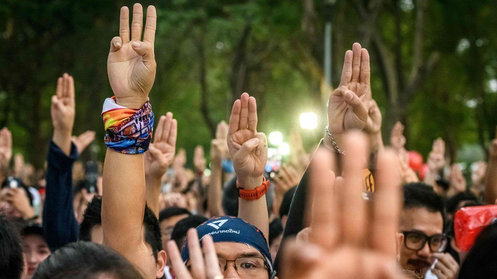 """Participants gesture a three-finger salute at the start of a """"run against dictatorship"""" in Bangkok"""
