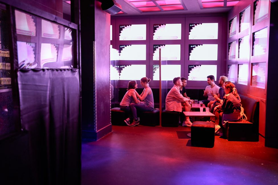People, separated by plastic screens, drink and chat at GAY, Soho, London. 4 July 2020