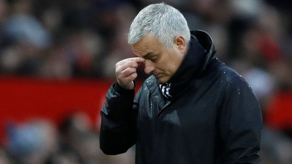 Mourinho pinches the bridge of his nose while standing on the field in this shallow depth of field shot from a football stadium